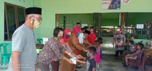 Kepala Desa, Erwin Sibagariang bersama para pendamping Desa dan apara saat membagikan secara simbolis makanan tambahan untuk anak-anak. Foto: istimewa